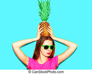 Fashion pretty woman in sunglasses with pineapple over blue background