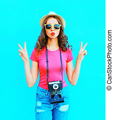 Fashion pretty woman wearing straw summer hat, sunglasses and vintage camera over colorful blue background