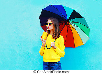 Fashion pretty woman with fresh fruit juice cup and colorful umbrella in autumn day over blue background wearing yellow knitted sweater