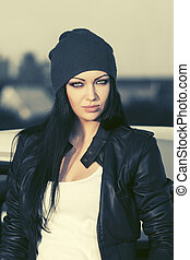 Fashion punk woman in leather jacket standing next to her car