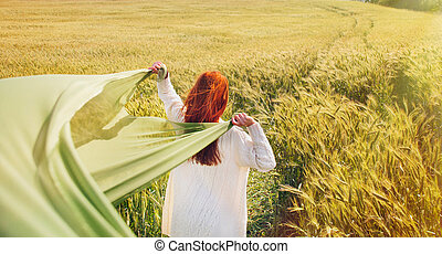 fashion red hair woman standing back hands up with green fabric in the field
