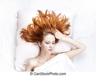 Fashion red-haired girl in the bedroom.