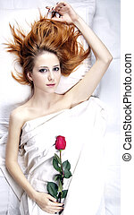 Fashion red-haired girl with rose in the bedroom.