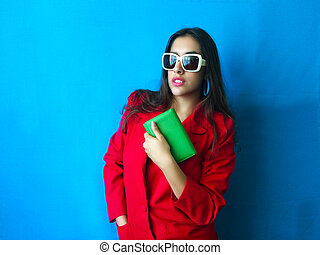 Fashion sexy model in white sunglasses beautiful woman with hands in her red coat and green handbag with long brunette hair and vintage retro and colorful clothes