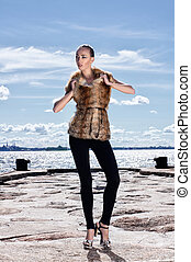 Fashion shoot of young attractive woman in fur dress