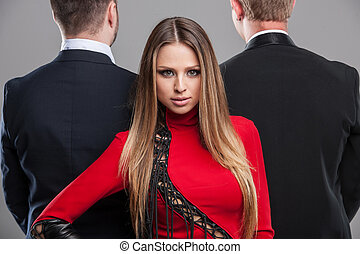 Fashion shoot Sexy blond stylish girl looking at camera. Two men in black suite standing on the background