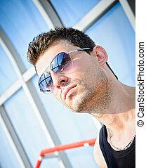 Fashion shot: closeup portrait of handsome young man wearing sunglasses