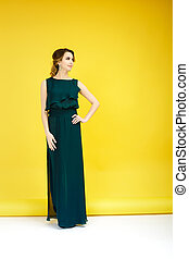 fashion shot of beautiful woman in green dress on yellow background