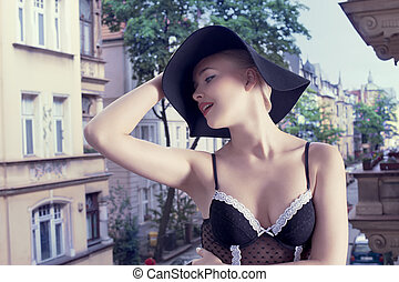 fashion shot of blond girl with hat and old town