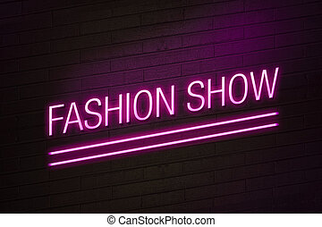 Pink neon sign with fashion show text on wall