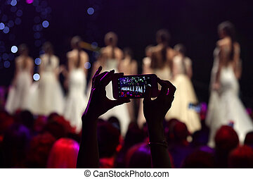 Fashion show runway taking picture with phone - A woman from...