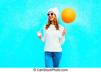 Fashion smiling woman holds an orange air balloon on blue background