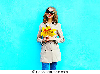 Fashion smiling woman with autumn yellow maple leaves wearing a coat on a blue background