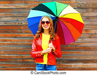 Fashion smiling woman with colorful umbrella in autumn day over wooden background