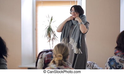 Fashion specialist teaches how to tie an oblong thick winter scarf.