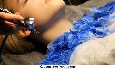 Fashion studio, the model is preparing for the show. Teen girl lies on a special couch, the designer prepares her image using a special airbrush spray with blue paint