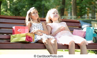 Fashion summer little girls in dresses sitting on a bench