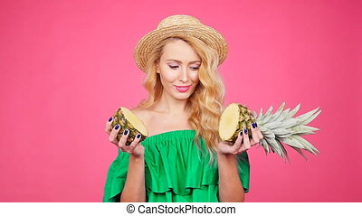 Fashion summer portrait of young pretty woman holding two big sweet pineapples