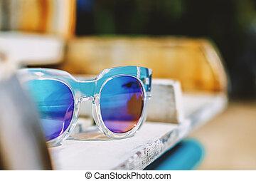 Fashion sunglasses on a beach chair, summer beach concept