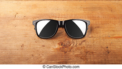fashion sunglasses on a wooden table.