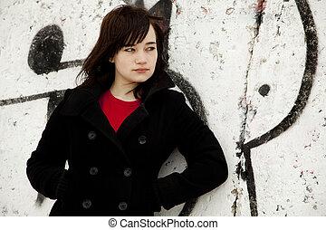 Fashion teen girl at white graffiti background.