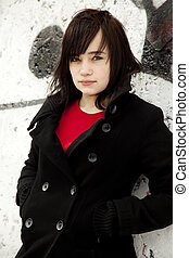 Fashion teen girl at white graffiti background.