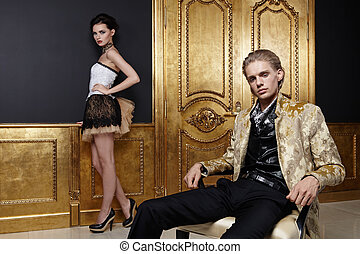Fashion - The young man sits on a forward background, behind...