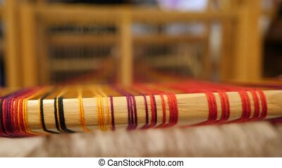 Wooden traditional vintage weaving hand loom with wool. Threads stretched like strings. Craftswomen on background. Handmade background. Manual wood loom. Hand loom background