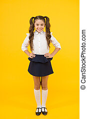 Fashion trends for back to school. Happy schoolchild with fashion look on yellow background. Small girl with long hair smiling in fashion uniform. Fashion for little student