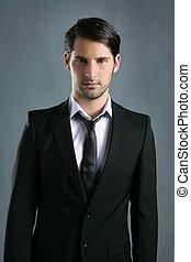 Fashion trendy elegant young black suit man posing looking...