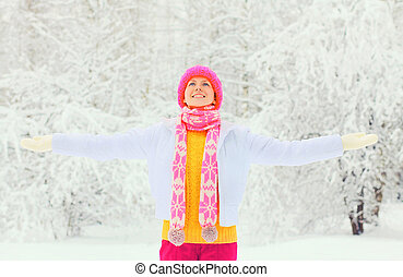 Fashion winter happy smiling woman wearing colorful knitted hat scarf enjoys over snowy background