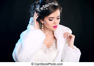 Fashion Winter portrait of beautiful girl  in white Fur Coat. Makeup. Hairstyle. Glamour young woman isolated on black background. Luxury Jewelry.