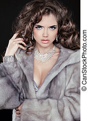 Fashion winter woman model wearing in mink fur coat with long wavy hair styling. Jewelry. Luxury life.