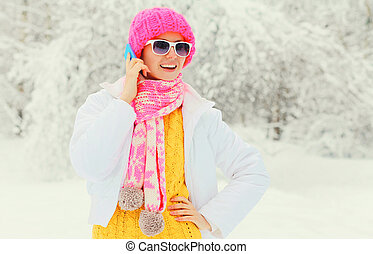 Fashion winter woman talking on smartphone wearing colorful knitted hat scarf over snowy trees