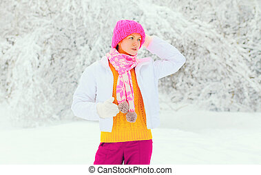 Fashion winter young woman wearing colorful knitted hat scarf over snowy background
