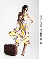 Beautiful fashion woman posing with a vintage suitcase