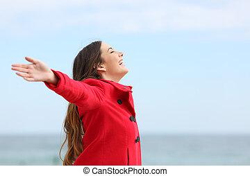 Happy fashion woman profile breathing deep fresh air in winter on the beach