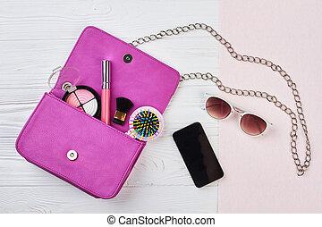 Fashion woman handbag with makeup accessories.