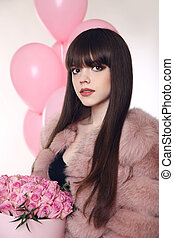 Fashion woman in fur coat, lady portrait over gift. Glamour brunette with rose bouquet of flowers in hat box over balloons isolated on white studio background.