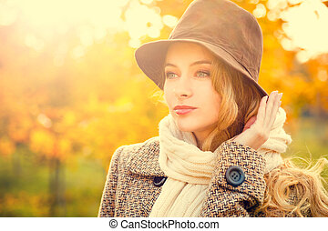 Fashion Woman in Hat on Yellow Autumn Background
