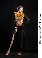 Fashion Woman in Luxury Fur Coat isolated over Black Background posing