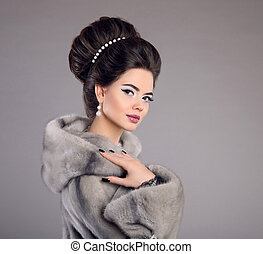 Fashion Woman in mink fur coat. Beauty makeup. Elegant hairstyle. Pearl jewelry women set. Glamour portrait of brunette girl model posing isolated on gray studio background.