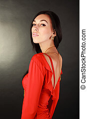 Fashion woman in red dress on black background in studio