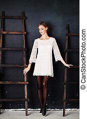 Fashion Woman in White Dress on Background. Studio Portrait