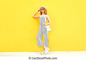 Fashion woman is posing in white striped pants, round hat on colorful yellow background