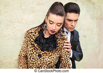 woman looking down while her boyfriend is touching her shoulder