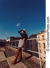 Fashion woman portrait of young pretty trendy girl in hat posing at the city in Europe, autumn street fashion.