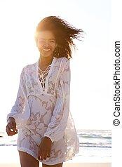 Fashion woman walking on beach with summer dress