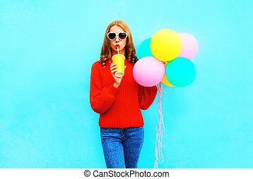 Fashion woman with an air balloons holds cup of fruit juice on blue background