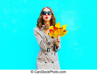 Fashion woman with autumn yellow maple leaves sends an air kiss on a blue background